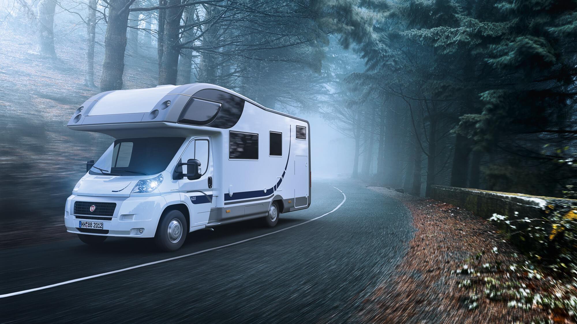 Caravan fährt auf Landstrasse durch einen Wald mit Nebel