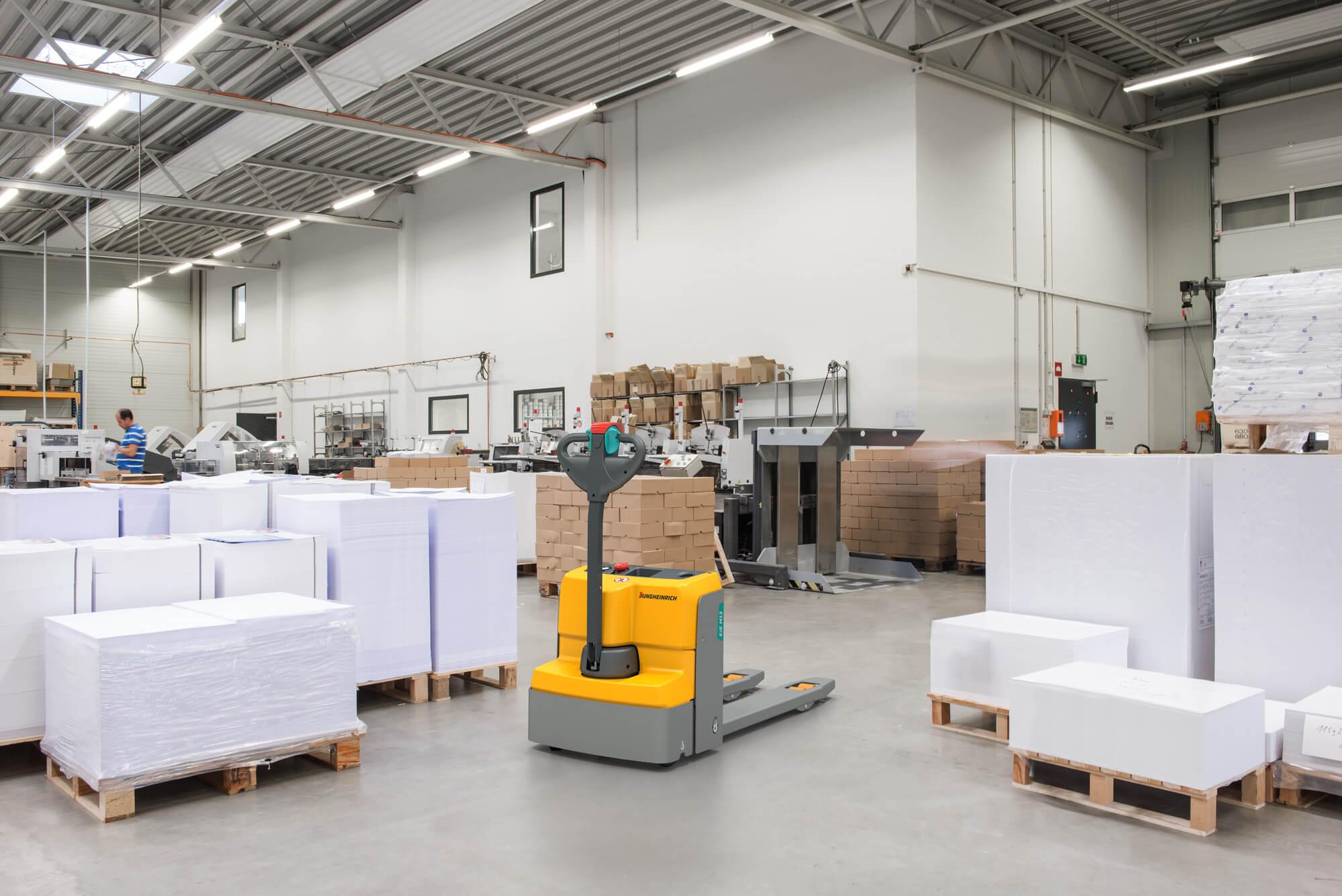 Jungheinrich EJC steht in Druckerei umgeben von Paletten mit Papier