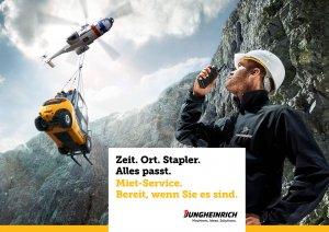 Hubschrauber fliegt mit Gabelstapler als hängende Last über Felsenwand