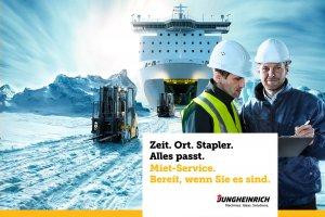 Gabelstapler fahren auf einer verschneiten Eisfläche aus der Ladeluke eines grossen Schiffes heraus.