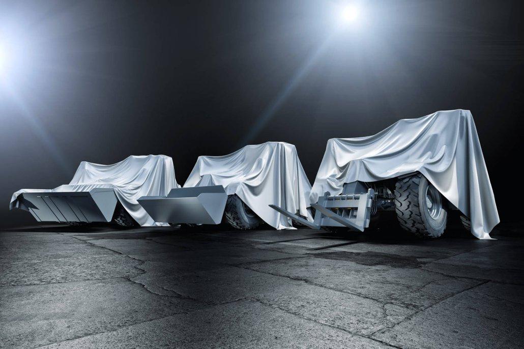 Drei mit Tüchern verhüllte Liebherr Teleskoplader im Scheinwerferlicht vor dunklem Hintergrund auf Asphalt