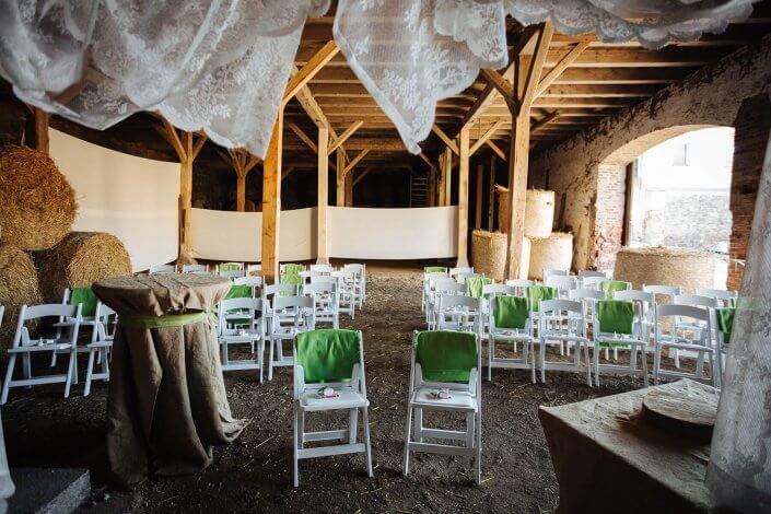 Weisse Stühle und Dekoration in einer Scheune für eine Hochzeit