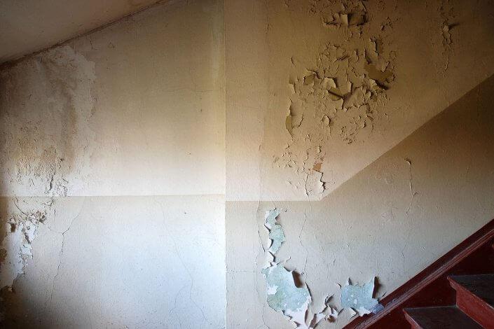 Abgeblätterte Wandfarbe und Schimmel in einem Treppenhaus